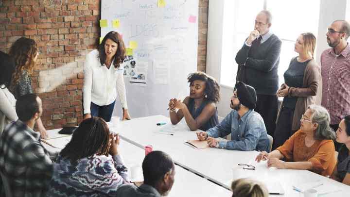 mujer-dando-instrucciones-en-una-reunion-de-trabajo